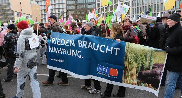 """UnterstützerInnen des Weltfriedensdienst auf der Agrardemo """"Wir haben es satt"""" mit einem Banner """"Frieden braucht Nahrung"""""""