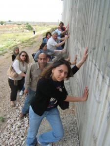Männer und Frauen stemmen sich gegen die israelische Mauer in den besetzten Gebieten