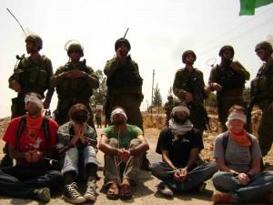 Israelische Soldaten stehen hinter am Boden sitzenden Menschen mit verbundenen Augen und gefesselten Händen