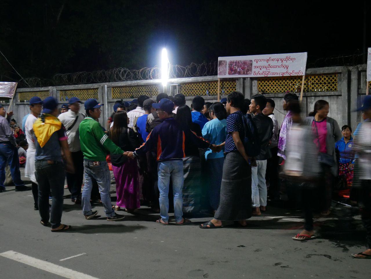 DemonstrantInnen bilden eine schützende Kette um einen der Führer der Protestbewegung. Myitkyina, 4.05.2018