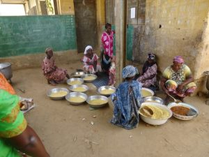 SchülerInnen sitzen auf dem Boden und essen