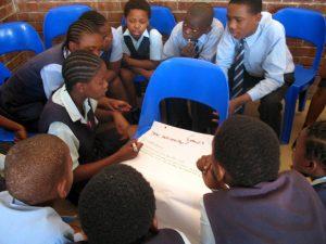 Jugendliche sitzen um einen Tisch herum