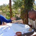 Shoki Mafogo und Vusi Tshabalala von Kruger2 Canyon (Südafrika) sitzen an einem Tisch und planen, wie sie Ressourcenkonflikte zur Sprache bringen können.