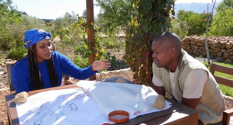 Shoki Mafogo und Vusi Tshabalala von Kruger2Canyon (Südafrika) sitzen an einem Tisch und planen, wie sie Ressourcenkonflikte zur Sprache bringen können.
